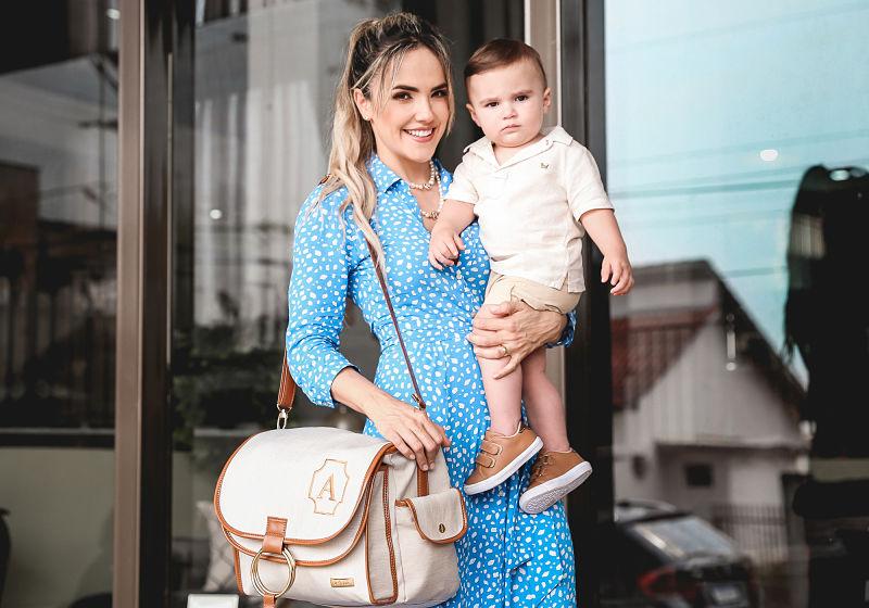 Modelo feminina com bebê no colo e bolsa de alça lateral