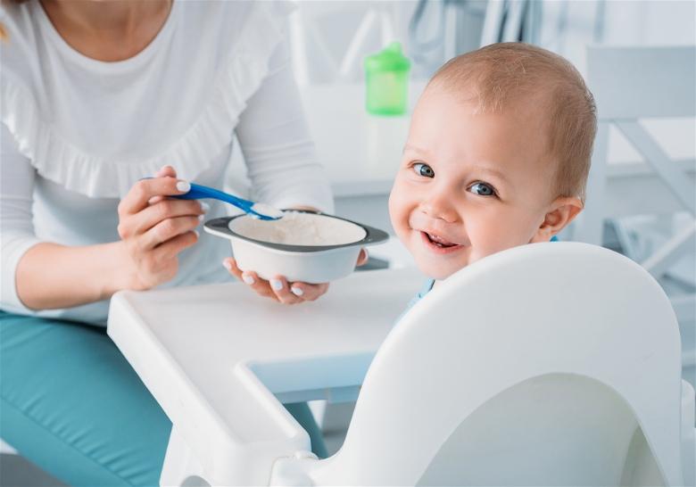 bebe sendo alimentado com papinha pela mãe