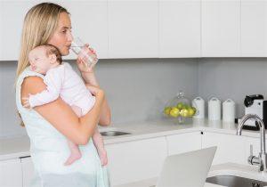 Mãe segurando bebe enquanto toma água