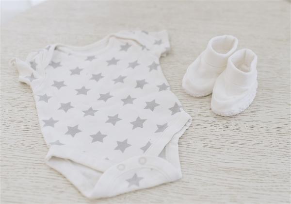roupa branca de bebe sobre a cama em destaque