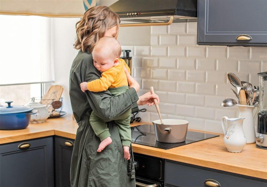 Mãe preparando alimentação pós parto com bebe no colo