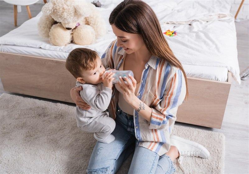 mãe amamentado bebe com mamadeira em seu colo