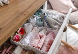 imagem de gaveta com roupas de bebe de diversas cores