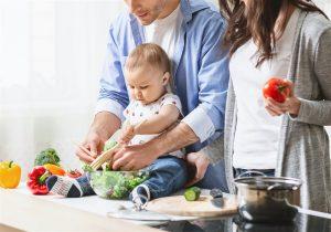 Homem e mulher lado a lado preparando salada de legumes enquanto bebe brinca com as folhagens