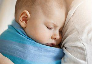 bebe dormindo no colo da mãe