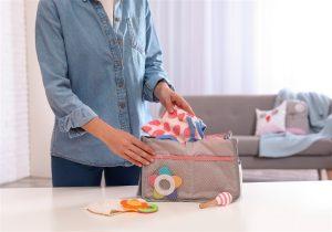 Imagem de mulher colocando roupinhas na bolsa