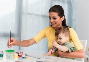 Mãe com bebe no colo enquanto faz pintura com tinta
