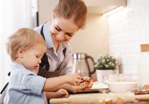 mãe e bebe na bancada da cozinha enquanto bebe brinca com alimentos