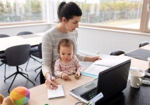 Mãe com bebe no colo enquanto faz tarefas à mesa do escritório
